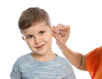 Mature woman putting hearing aid in little grandson`s ear on white background. Closeup stock images