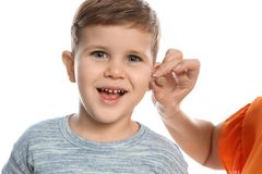 Mature woman putting hearing aid in little grandson`s ear on white background stock photography