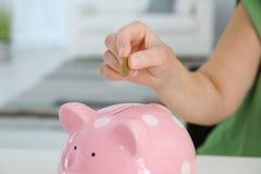 Mature woman putting money into piggy bank indoors stock photo