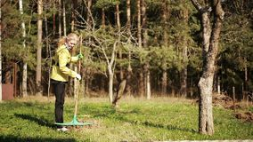 Mature woman raking leaves in a garden. On the background of spring forest stock video footage
