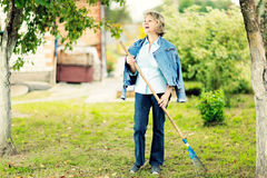 Mature woman raking leaves in her garden laughing. Royalty Free Stock Images