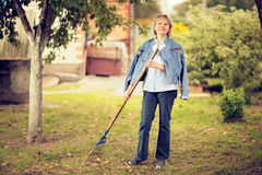 Mature woman raking leaves in her garden looking at camera and smiling.