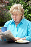 Mature woman reacts to newspaper Stock Image