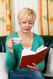 Mature woman is reading a book. And is drinking a cup of coffee Stock Photo