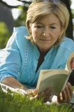 A mature woman reading a book. stock photography