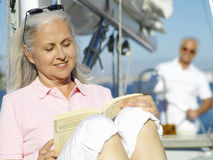 Mature woman reading book on boat, man in background Stock Photography
