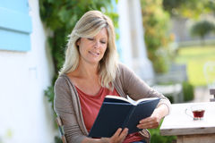 Mature woman reading book and drinking coffee Royalty Free Stock Images