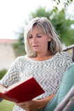 Mature woman reading book in garden Royalty Free Stock Photo
