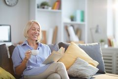 Mature Woman Reading Book at Home stock photography