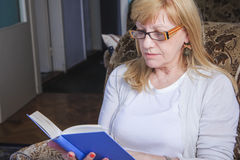 Mature woman reading a book Stock Images
