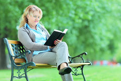 Mature woman reading a book in park seated on bench Royalty Free Stock Photos