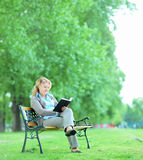 Mature woman reading a book in park Royalty Free Stock Image