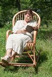 Mature woman reading book in rocking chair Stock Photo