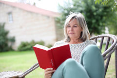 Mature woman reading book sitting in garden Stock Images