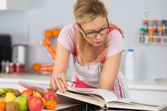 Mature woman reading cookbook in kitchen looking for recipe Stock Photos