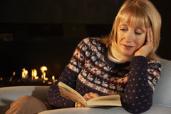Mature woman reading in front of fire at home Stock Image