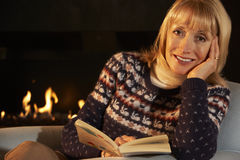 Mature woman reading in front of fire at home Stock Images