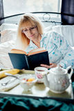 Mature Woman Reading Having Breakfast in Bed Stock Photo