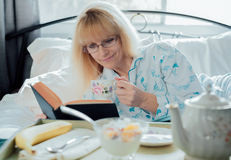 Mature Woman Reading Having Breakfast in Bed Royalty Free Stock Image