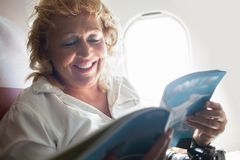 Mature Woman Reading Magazine on a Plane Stock Photo