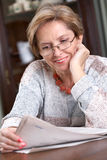 Mature woman reading newspaper Stock Photos