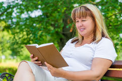 Mature woman reading a novel stock images