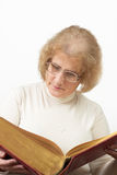 Mature woman reading old book/Bible. Mature age woman with glasses sits while reading old red paperback book/Bible Royalty Free Stock Photo
