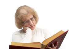 Mature woman reading old book/Bible. Mature age woman with glasses sits while reading old red paperback book/Bible Royalty Free Stock Photos