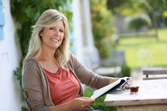 Mature woman reading in terrace Stock Photo