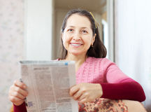 Mature woman reads newspaper Royalty Free Stock Photo