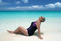 Mature woman reclines on pristine beach. Mature woman lies back and enjoys the sun at waters edge; turks and caicos Stock Image