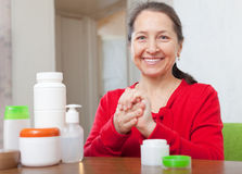 Mature woman in red applying cream on hands Royalty Free Stock Image