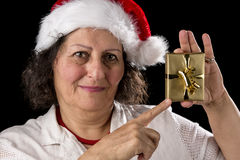 Mature Woman with Red Cap Pointing at Golden Gift. Friendly, venerable, dark-haired woman wearing an Old Father Christmas cap. She is pointing with her right Stock Image