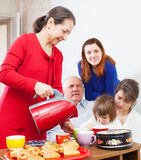 Mature woman in red pours tea Stock Photos