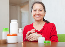 Mature woman in red puts cream on hands Royalty Free Stock Images