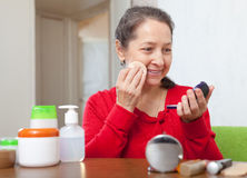 Mature woman  in red  putting facepowder Stock Image