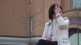 Mature woman relax on the bench in park. Senior woman waits someone. She`s touching her hair and looks around her. Prores codec stock video