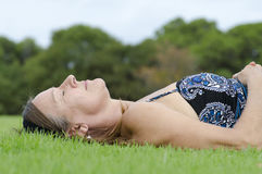Mature Woman relaxed on grass Stock Images