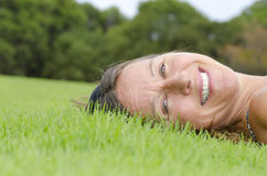 Mature Woman relaxed on grass Royalty Free Stock Images
