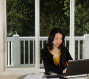 Mature woman relaxed while working from home Royalty Free Stock Photos