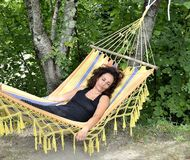 Mature woman relaxes on a hammock. Stock Photos