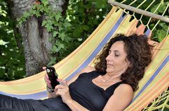 Mature woman relaxes on a hammock. Stock Photo