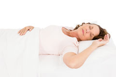 Mature woman relaxing on bed. Against white background Royalty Free Stock Photos