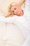Mature woman relaxing in bed stock photos