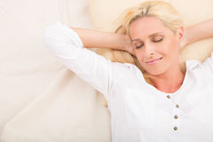 Mature woman relaxing in bed royalty free stock images
