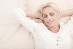 Mature woman relaxing in bed Stock Images
