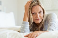Mature woman relaxing on bed stock photos