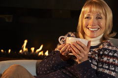 Mature woman relaxing in front of fire at home Royalty Free Stock Image