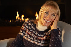 Mature woman relaxing in front of fire at home Royalty Free Stock Photography