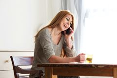 Mature woman relaxing at home with tea and phone. Portrait of a smiling mature woman drinking green tea at home and using mobile phone Stock Photos